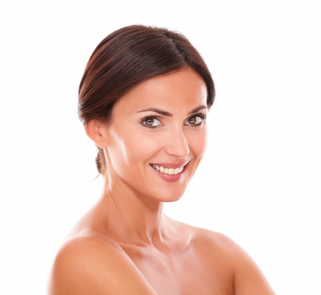 Stylized head and shoulders portrait of candid hispanic woman with brown eyes smiling at camera with nude shoulders on isolated studio