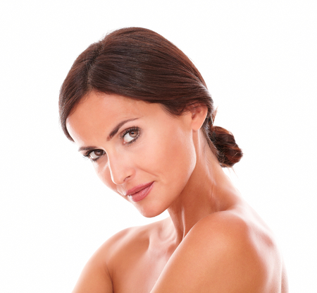 Head and shoulders portrait of adult latin female showing her sensual look with nude shoulders while looking at camera on isolated studio