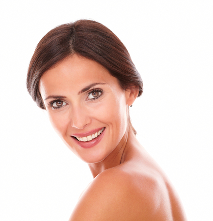 Candid portrait of sexy and beautiful woman smiling at camera with nude shoulders on isolated studio