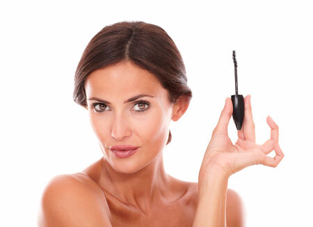 Close up portrait of young woman for mascara product with nude shoulders looking at camera on isolated studio Stock Photo