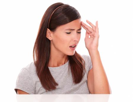 ojos cerrados: Mujer bonita que sufren de dolor de cabeza con los ojos cerrados sobre fondo blanco