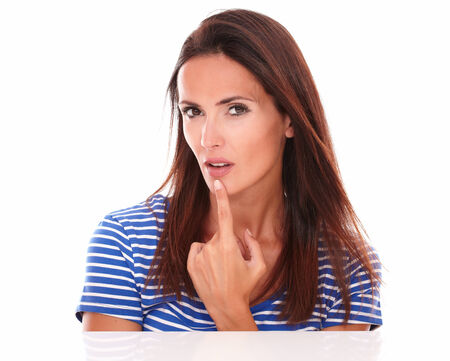 wondering: Lovely brunette looking at camera wondering about a question in white background