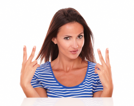 Lovely brunette looking at camera smiling while making a victory sign with fingers up in white background photo