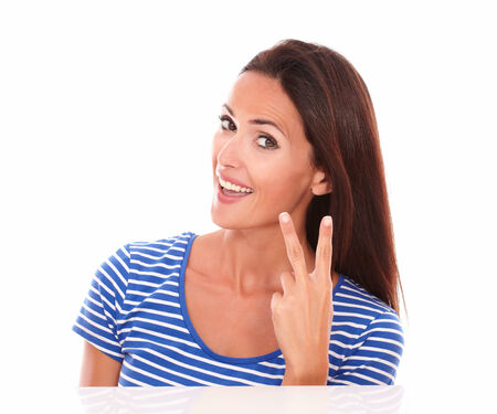 Smiling young woman with fingers up and feeling a winner in white background photo