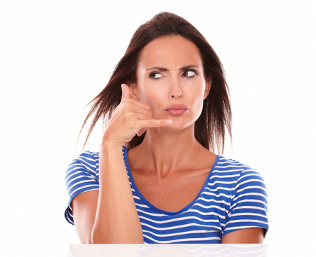 wondering: Beautiful brunette wondering about a phone call in white background