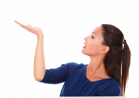 Charming lady in blue shirt holding right palm up while looking to her right in white background - copyspace photo