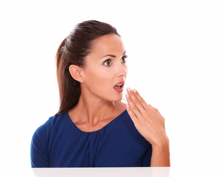 Beautiful woman in blue blouse looking surprised with hand on mouth while looking to her left in white background - copyspace photo