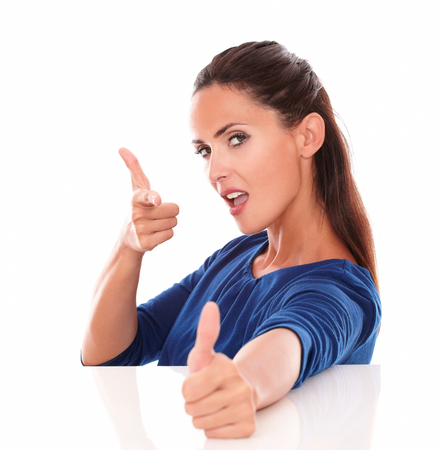 Young lady gesturing shooting a thumb up while looking at you in white background photo