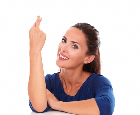 crossing fingers: Friendly female smiling and crossing fingers while looking at you in white background