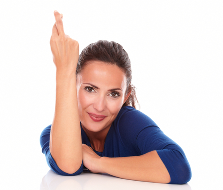 crossing fingers: Cute woman smiling and crossing fingers while looking at you in white background