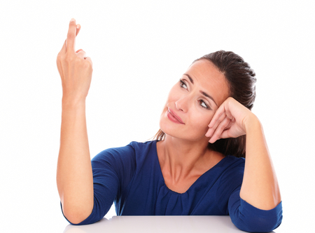 crossing fingers: Attractive woman smiling and crossing fingers while looking to her right in white background Stock Photo