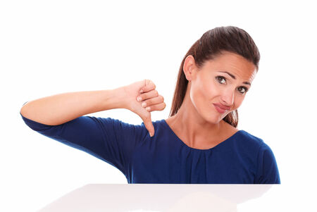 Disappointed young female with thumb down, gesturing bad job, while looking at you in white background photo