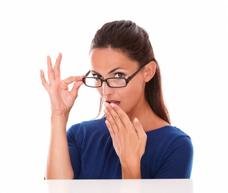 Shy girl looking at you embarrassed with hand on mouth in white background photo
