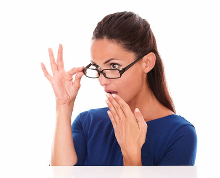 Shy girl looking embarrassed with hand on mouth looking over glasses in white background - copyspace photo