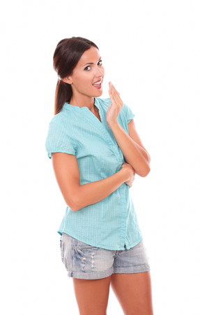 30 34 years: Latin girl in short jeans looking at you surprised with hand on mouth standing in white background - copyspace