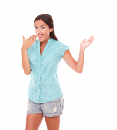 30 34 years: Stylish woman in short jeans gesturing excitement while looking at you with hand on mouth, standing in white background - copyspace