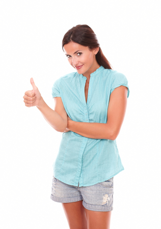 30 34 years: Cheerful woman looking at you with thumb up gesturing ok sign while standing in white background