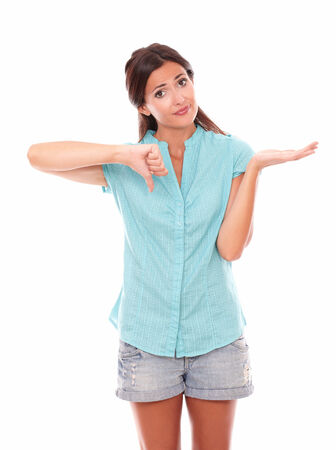 Latin girl with thumb down while standing and looking at you front view in white background photo