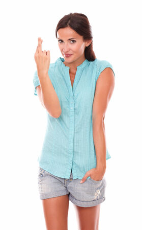 crossing fingers: Smiling female with crossing fingers for luck sign while looking at you in white background