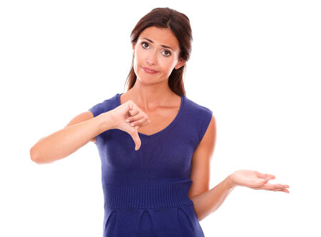 Sad latin lady with thumb down gesturing a bad job while looking at you disappointed in white background photo