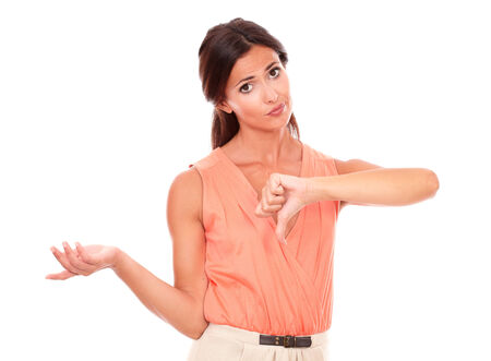 Pretty young female with thumb down gesturing a bad job while looking at you disappointed and unhappy in white background - copyspace photo