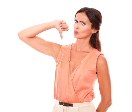 Pretty young lady with thumb down gesturing a bad job while looking at you disappointed and unhappy in white background photo