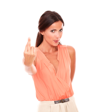 crossing fingers: Attractive latin woman with crossing fingers gesturing a luck sign and making a wish while looking at you in white background
