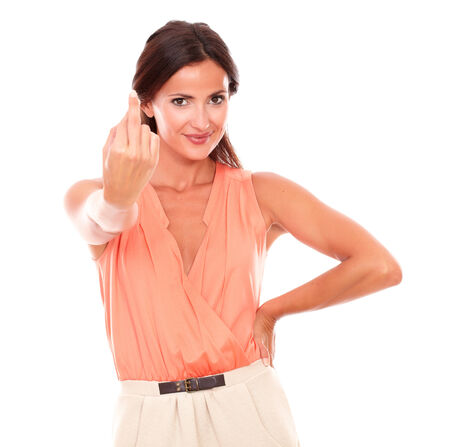 Lovely young woman with crossing fingers gesturing a luck sign and making a wish while looking at you in white background photo