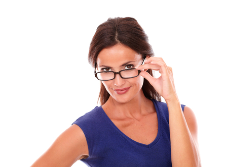 30 34 years: Cheerful woman in purple dress looking over spectacles while smiling in white background Stock Photo