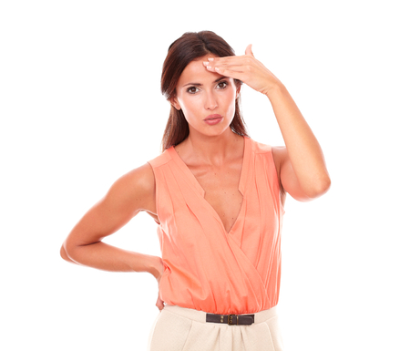 Lovely lady suffering from migraine headache with hand on head and looking at you in white background
