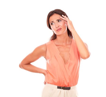 Lovely female suffering from migraine headache with hand on head and looking to her right in white background - copyspace