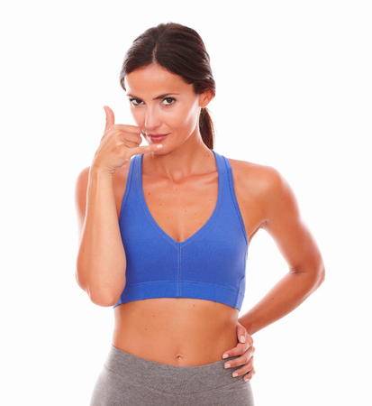 attractive charismatic: Sporty young woman gesturing phone call on isolated background Stock Photo