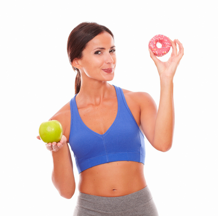 tempting: Hungry fit woman in training clothes tempting to eat while looking at you on isolated background
