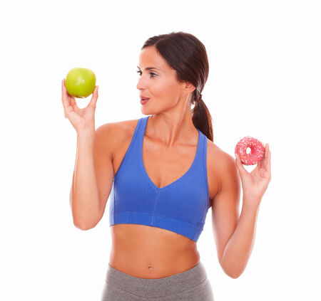 eat right: Sporty adult woman smiling at the fruit held by her right hand on isolated background