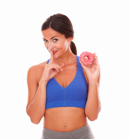 secretly: Fit lady in training wear secretly eating sugary food against white background - copyspace