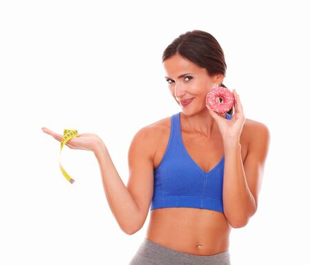 Slim woman wearing training clothes and trying to lose weight on isolated background photo