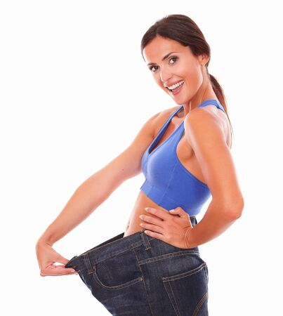 weight control: Fit latin woman pulling jeans on waist while looking at you cheerfully with weight loss achievement on isolated background