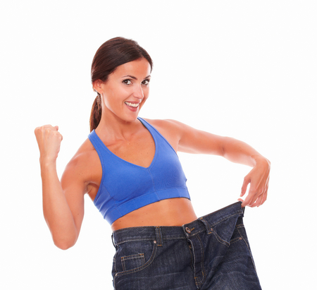 Hispanic brunette cheerfully pulling her jeans to measure waist on isolated background photo