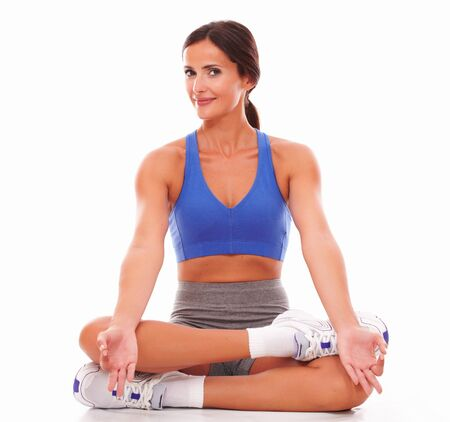 30s adult: Sporty young woman doing relaxation exercise against white background Stock Photo