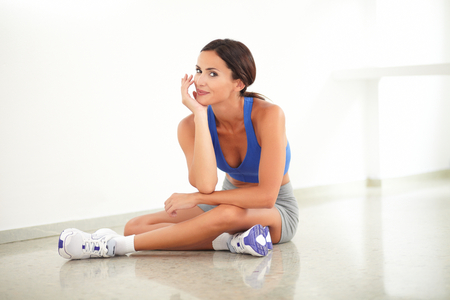 Pretty young female in training clothes sitting in yoga class while looking at you at gym Stock Photo