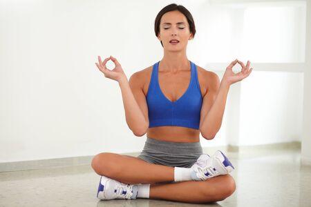 ojos cerrados: Mujer bonita que hace ejercicio de relajaci�n mientras que sonr�e con los ojos cerrados Foto de archivo