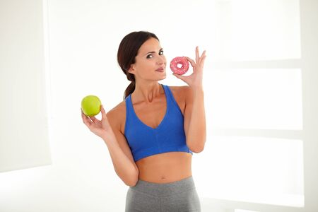 deciding: Sporty pretty lady deciding between donut and apple for diet while looking at you
