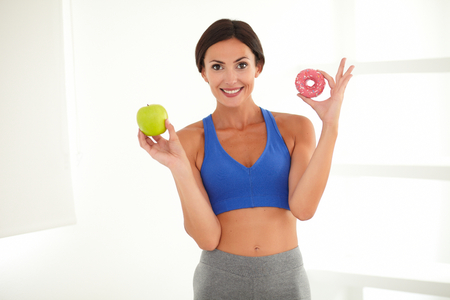deciding: Smiling sporty lady on a diet deciding between apple and sugary donut while looking at you Stock Photo
