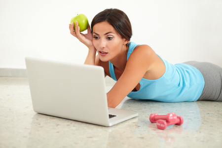 sports clothing: Adult lady in sports clothing laying and surfing the web Stock Photo
