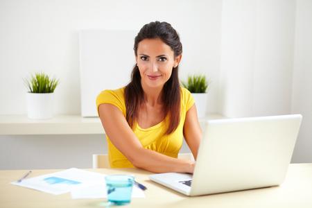 recepcionista: Trabajar como recepcionista en una empresa, mientras que usa su computadora port�til femenina bonita Foto de archivo