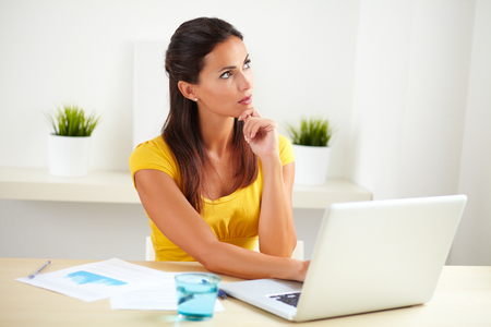 wondering: Pretty receptionist wearing yellow clothes and wondering in her office Stock Photo