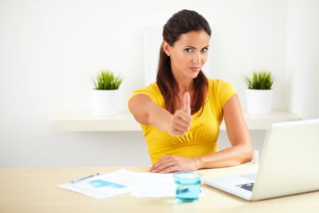 great job: Happy company boss in yellow clothes showing you a great job sign in her workplace - copyspace Stock Photo