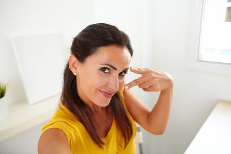 webcam: Attractive woman chatting on a webcam while cheerfully smiling Stock Photo