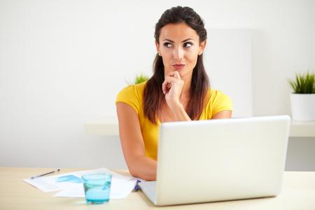mujer pensando: Empleado hispano pensativo de una empresa de negocios que trabaja en su computadora port�til en la oficina - copyspace