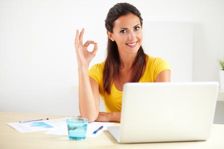 ながら彼女のオフィスで働くビジネス会社の秘書の素敵な満足している表示されている場合正のフィードバックの看板 - copyspace 写真素材